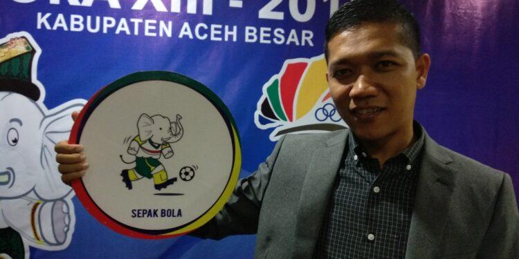 Seorang model menunjukkan Gajah Puteh, maskot PORA XIII yang sedang main bola