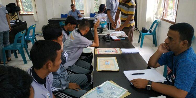 Direktur Teknik Edi Darman sedang memeriksa keabsahan identitas pemain pada screening test cabor Futsal di Aula Kantor Camat Jantho, Minggu (18/11). Foto Humas PORA
