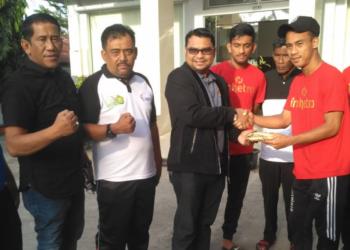 Kadispora Aceh Dedy Yuswadi menyerahkan bonus kepada kapten tim sepakbola Porwil | Foto: Ist