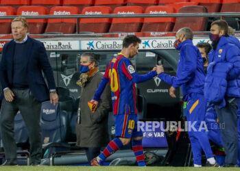 Bintang Barcelona Lionel Messi (tengah), meninggalkan lapangan melewati pelatih Barca Ronald Koeman (kiri).