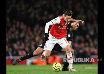 Rodrigo menempel ketat Mesut Ozil pada laga antara Arsenal melawan Manchester City di Etihad Stadium, London, Ahad (15/12).