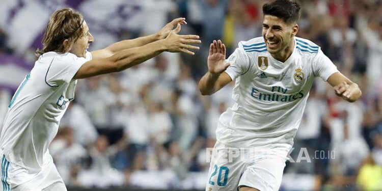 Striker Real Madrid Marco Asensio (kanan) merayakan golnya dengan rekan setimnya Luka Modric pada pertandingan leg ke-2 Piala Super Spanyol antara Real Madrid vs Barcelona FC di Stadion Santiago Bernabeu, Madrid, Spanyol, Kamis (17/8) pagi.