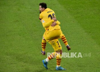 Pemain Barcelona Lionel Messi merayakan gol ketiga timnya, bersama rekan setimnya Antoine Griezmann pada pertandingan sepak bola La Liga Spanyol antara Athletic Bilbao dan Barcelona di stadion San Mames di Bilbao, Spanyol, Kamis (7/1) dini hari WIB.