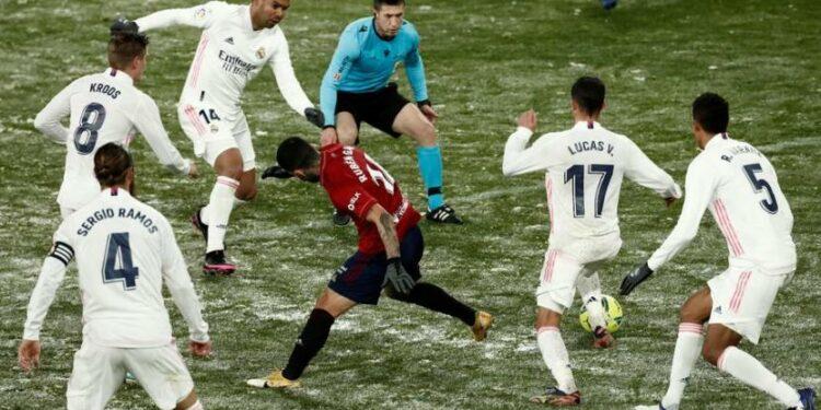 Gelandang Osasuna, Ruben Garcia (tengah), dikepung pemain Real Madrid dalam laga La Liga Spanyol yang bersalju di Stadion El Sadar, Pamplona, Sabtu (9/1). Real Madrid gagal menggeser Osasuna dari puncak klasemen.