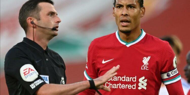 Virgil van Dijk (kanan) dari Liverpool berbicara dengan wasit Michael Oliver (kiri).