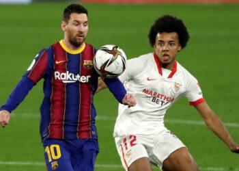 Kapten Barcelona Lionel Messi berduel dengan pemain Sevilla Jules Kounde dalam pertandingan leg pertama semifinal Copa del Rey di Stadion Ramon Sanchez Pizjuan, Kamis (11/2) dini hari WIB.