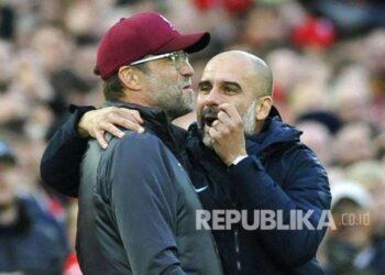 Manajer City Josep Guardiola (kanan) dan manajer Liverpool Juergen Klopp berbicara di tengah pertandingan Liga Inggris antara Liverpool melawan Manchester City di Stadion Anfield, Liverpool, Senin (8/10)