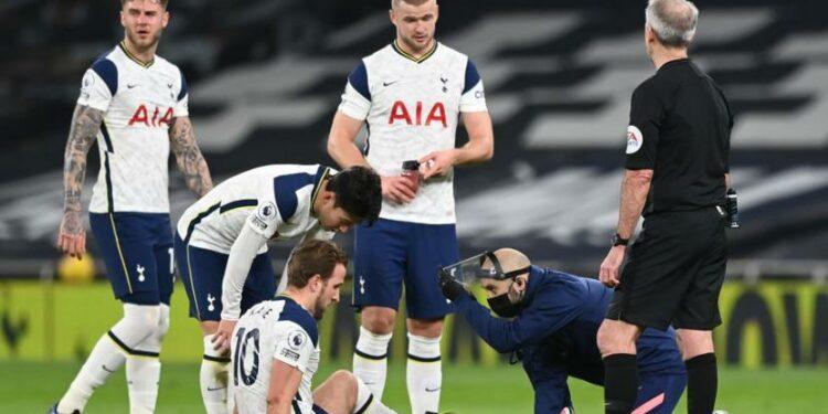 Penyerang Tottenham Hotspur Harry Kane (duduk) menerima perawatan di tengah laga kontra Liverpool. Kane mengalami cedera engkel.