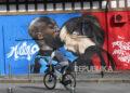 Seorang pengendara sepeda melihat mural di dekat Stadion Giuseppe Meazza, yang menggambarkan Romelu Lukaku (kiri) dari Inter Milan dan Zlatan Ibrahimovic dari AC Milan bertengkar saat pertandingan Piala Italia, di Milan, Italia, 15 Februari 2021. Inter Milan dan AC Milan akan bermain melawan satu sama lain pada 21 Februari 2021 dalam pertandingan puncak Serie A Italia.