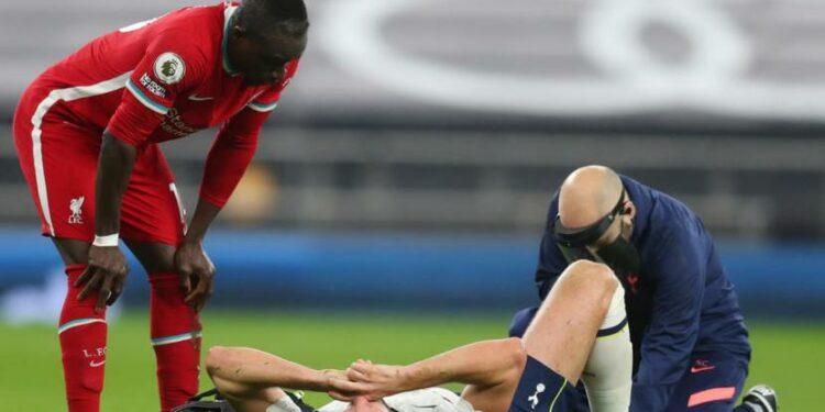Penyerang Tottenham Hotspur Harry Kane (berbaring) mendapatkan perawatan dalam pertandingan melawan Liverpool