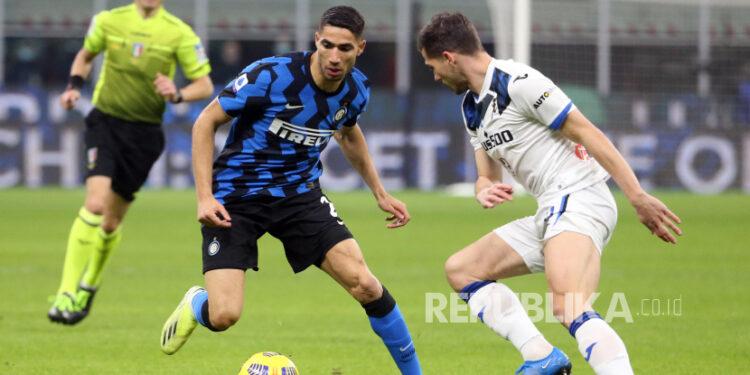 Achraf Hakimi (kiri) dari Inter beraksi melawan Remo Freuler (kanan) dari Atalanta pada pertandingan sepak bola Serie A Italia antara Inter Milan dan Atalanta Bergamo di stadion Giuseppe Meazza di Milan, Italia, 08 Maret 2021.