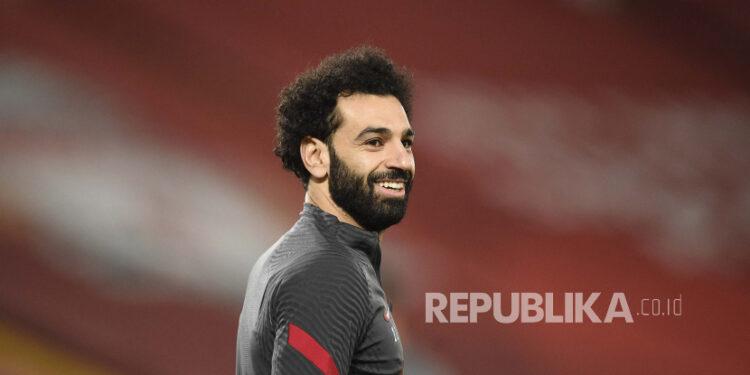 Mohamed Salah dari Liverpool tersenyum saat melakukan pemanasan sebelum dimulainya pertandingan sepak bola Liga Premier Inggris antara Liverpool dan Chelsea di stadion Anfield di Liverpool, Inggris, Kamis, 4 Maret 2021.