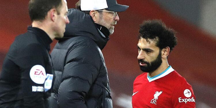 Mohamed Salah berjalan melewati manajer Liverpool Juergen Klopp saat pergantian pemain di laga Liverpool vs Chelsea, Jumat (5/3).