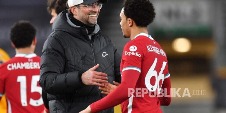 Manajer Juergen Klopp dari Liverpool bereaksi dengan pemainnya Trent Alexander-Arnold (kanan) setelah pertandingan sepak bola Liga Premier Inggris antara Wolverhampton Wanderers dan Liverpool FC di Wolverhampton, Inggris, 15 Maret 2021.