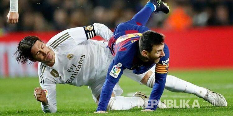 Bek Real Madrid Sergio Ramos mengganjal Lionel Messi.