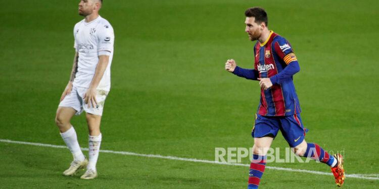 Striker FC Barcelona Leo Messi (kanan) melakukan selebrasi setelah mencetak gol melawan SD Huesca selama pertandingan sepak bola LaLiga Spanyol antara FC Barcelona dan SD Huesca yang diadakan di stadion Camp Nou, di Barcelona, ??Catalonia, Spanyol, 15 Maret 2021.