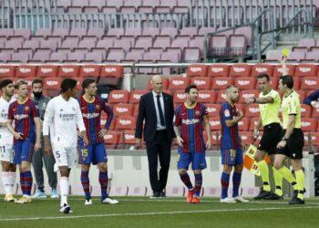 Wasit Juan Martinez Munuera (kanan) memberikan kartu kuning kepada pemain Barcelona Jordi Alba dalam laga El Clasico kontra Real Madrid, Sabtu (24/10). Juan Martinez mendapatkan kritikan dari pihak Barcelona atas kepemimpinannya dan harian Sport melaporkan, ayahnya merupakan pendiri fan klub Real Madrid.