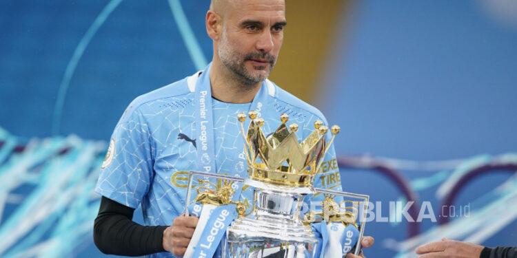 Manajer Manchester City Pep Guardiola merayakan dengan trofi setelah memenangkan Liga Premier Inggris, Ahad (23/5).