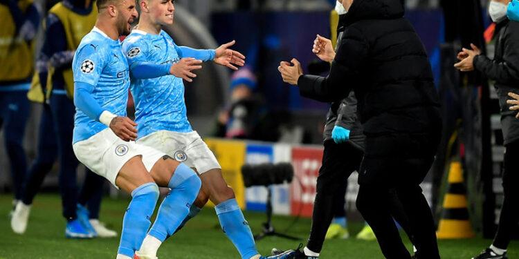 Phil Foden (tengah) merayakan golnya bersama pelatih Manchester City Pep Guardiola (R). Golnya membuat City unggul 2-1 pada leg kedua perempat final Liga Champions melawan Dortmund, Kamis (15/4).