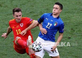Pemain Wales Aaron Ramsey (kiri) dan pemain Italia Giacomo Raspadori berebut bola pada pertandingan grup A kejuaraan sepak bola Euro 2020 antara Italia dan Wales di stadion Stadio Olimpico di Roma, Ahad (20/6).