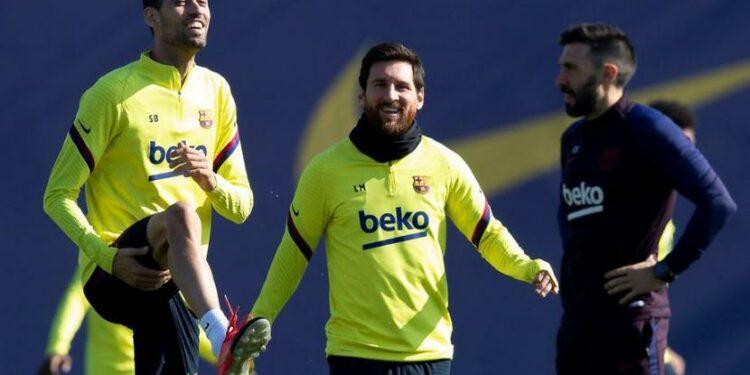 Sergio Busquets (kiri) dan Lionel Messi (tengah).