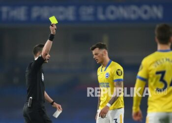 Wasit Stuart Attwell (kiri) menunjukkan kartu kuning kepada pemain Brighton Ben White (tengah) pada pertandingan sepak bola Liga Utama Inggris antara Chelsea dan Brighton dan Hove Albion di Stadion Stamford Bridge di London, Rabu (21/4) dini hari WIB.