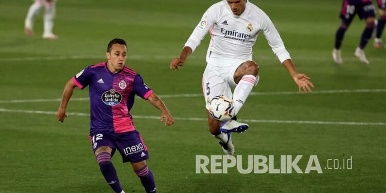 Bek Real Madrid Raphael Varane (kanan) beraksi melawan pemain sayap Valladolid Fabian Orellana (kiri) pada pertandingan LaLiga Santander Spanyol antara Real Madrid dan Real Valladolid di stadion Alfredo Di Stefano di Madrid, Spanyol (30/9/2020).