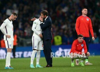 Pelatih kepala Gareth Southgate (tengah) dari Inggris menghibur Jadon Sancho setelah gagal mencetak gol saat adu penalti pada final UEFA EURO 2020 antara Italia dan Inggris di London, Inggris, Senin (12/7) dini hari WIB.