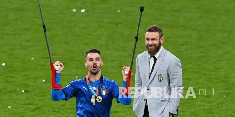 Pemain Italia Leonardo Spinazzola yang cedera pada awal turnamen melakukan selebrasi setelah Italia memenangkan final UEFA EURO 2020 antara Italia dan Inggris di London, Inggris, Senin (12/7) dini hari WIB.. Di sebelah kanan adalah Angelo de Rossi, anggota staf pelatih Italia.