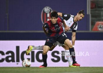 Pemain Juventus Cristiano Ronaldo berusaha berebut bola dengan pemain Bologna Takehiro Tomiyasu (depan) pada pertandingan sepak bola Serie A Liga Italia.