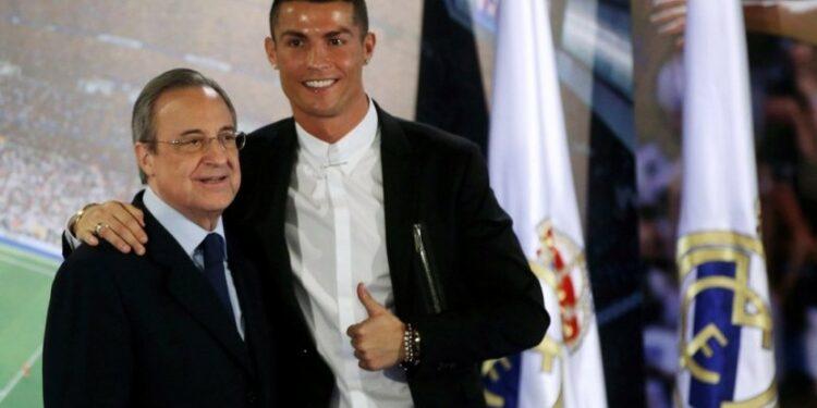 Cristiano Ronaldo (kanan) berpose dengan Presiden Real MAdrid Florentino Perez dalam seremoni perpanjangan kontrak CR7 di Santiago Bernabeu, Senin (7/11).
