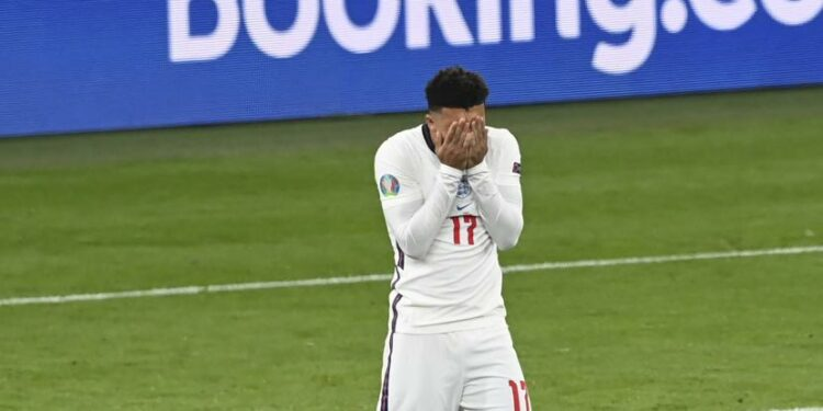 Reaksi pemain Inggris Jadon Sancho setelah kehilangan peluang untuk mencetak gol dalam adu penalti pada pertandingan final sepak bola Euro 2020 antara Italia dan Inggris di stadion Wembley di London, Minggu, 11 Juli 2021.