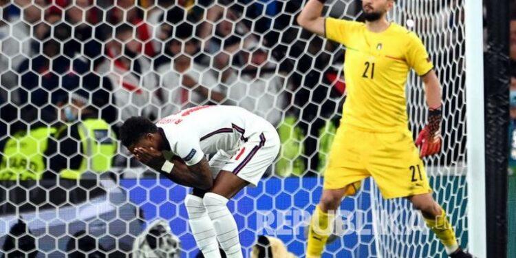 Marcus Rashford (kiri) dari Inggris bereaksi setelah gagal mengeksekusi penalti saat adu penalti di final Euro 2020 antara Italia dan Inggris di London, Inggris, Senin (12/7) dini hari WIB.