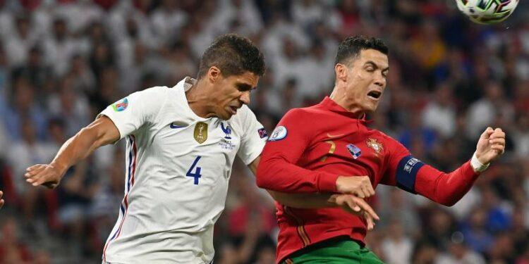 Cristiano Ronaldo dari Portugal (kanan) beraksi melawan Raphael Varane dari Prancis selama pertandingan sepak bola babak penyisihan grup F UEFA EURO 2020 antara Portugal dan Prancis di Budapest, Hongaria, 23 Juni 2021.