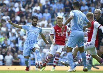 Gelandang Manchester City Ilkay Guendogan (kiri) berebut bola dengan pemain Arsenal. Guendogan mencetak gol pertama City melawan Arsenal dalam lanjutan Liga Primer Inggris, Sabtu (28/8).