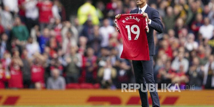 Raphael Varane menunjukkan kausnya kepada para penggemar setelah menandatangani kontrak dengan Manchester United menjelang pertandingan sepak bola Liga Premier Inggris antara Manchester United dan Leeds United di Old Trafford di Manchester, Inggris, Sabtu, 14 Agustus 2021.