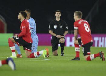 Wasit Andy Madley, tengah, dan para pemain berlutut untuk mendukung gerakan Black Lives Matter sebelum pertandingan sepak bola Liga Primer Inggris antara Southampton dan West Ham United di Stadion St. Mary di Southampton, Inggris, Selasa, 29 Desember 2020.