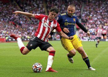 Tino Livramento dari Southampton, kiri, dan Luke Shaw dari Manchester United selama pertandingan sepak bola Liga Premier Inggris mereka di Stadion St. Mary di Southampton, Inggris, Minggu 22 Agustus 2021.