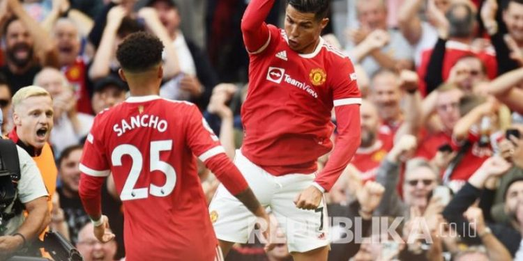 Pemain Manchester United  Cristiano Ronaldo (kanan) merayakan mencetak gol kedua timnya dengan Jadon Sacho pada pertandingan sepak bola Liga Premier Inggris antara Manchester United dan Newcastle United di Manchester, Inggris, Sabtu (11/9).