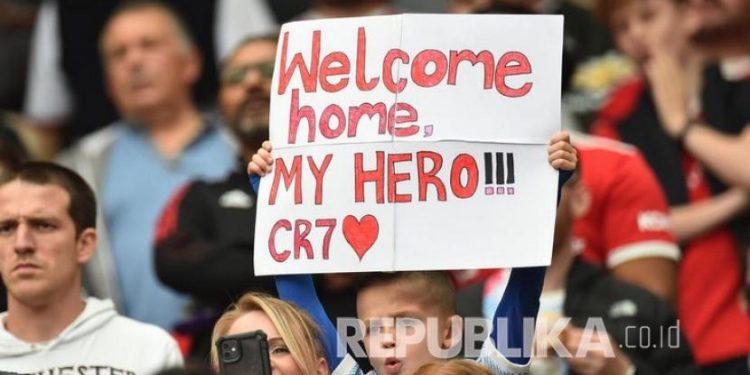 Suporter Manchester United memegang poster yang berhubungan dengan Cristiano Ronaldo menjelang pertandingan sepak bola Liga Inggris antara Manchester United dan Newcastle United di Manchester, Inggris, Sabtu (11/9).