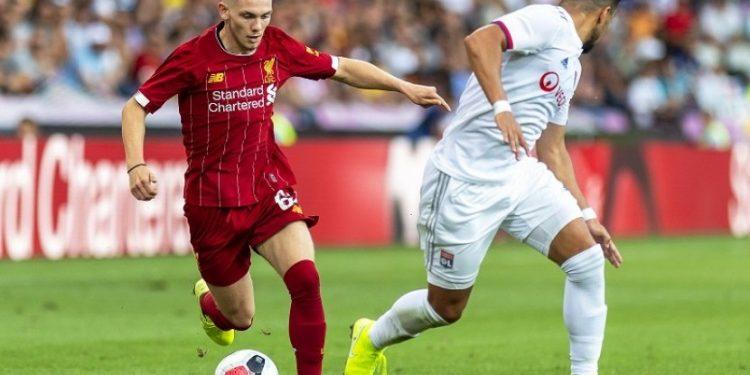 Pemain Liverpool Harvey Elliott (kiri) menggiring bola melewati pemain Olympique Lyon Rafael Pereira Da Silva dalam laga persahabatan di Jenewa, Swiss, Kamis (1/8) dini hari WIB.