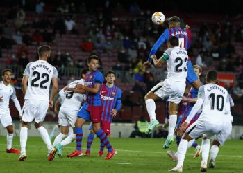 Pemain Barcelona Ronald Araujo melakukan sundulan di sebelah pemain Granada Jorge Molina selama pertandingan sepak bola La Liga Spanyol antara Barcelona dan Granada, at the Camp Nou stadium in Barcelona, Spanish, Tuesday (21/9).