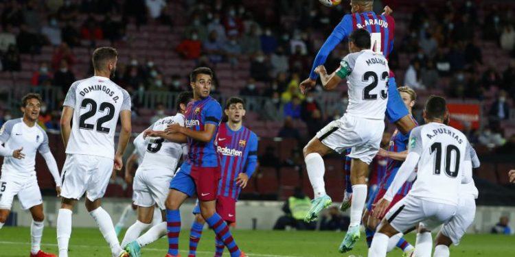 Pemain Barcelona Ronald Araujo melakukan sundulan di sebelah pemain Granada Jorge Molina selama pertandingan sepak bola La Liga Spanyol antara Barcelona dan Granada, di stadion Camp Nou di Barcelona, Spanyol, Selasa (21/9).