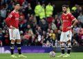 Pemain Manchester United Bruno Fernandes dan Cristiano Ronaldo, kiri, bereaksi setelah pemain Liverpool Mohamed Salah mencetak gol ketiga timnya pada pertandingan sepak bola Liga Premier Inggris antara Manchester United dan Liverpool di Old Trafford di Manchester, Inggris, Ahad (24/10)